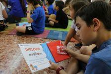 Un infant rep el seu diploma com a membre del club mir@llibres